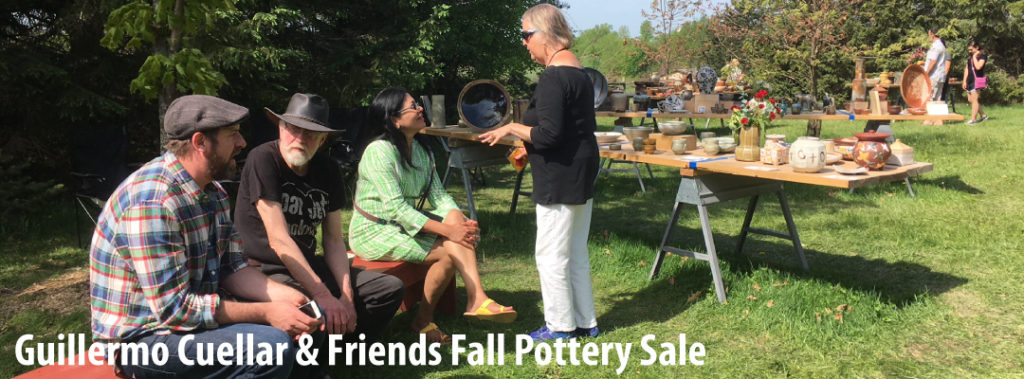 potters and guests chat while tables of functional pottery spread out on a lawn are in the background.