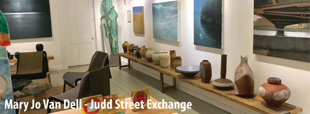 Image of Judd Street Exchange gallery with paintings, pottery and seating area for guests.